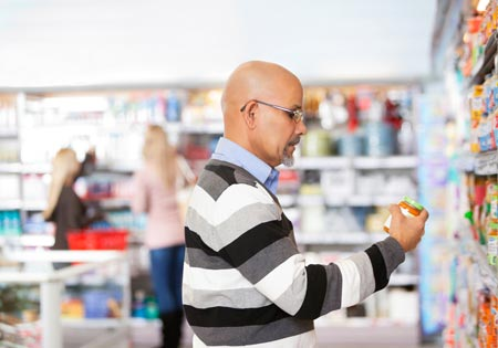 Image of a man looking at different products in a grocery store.